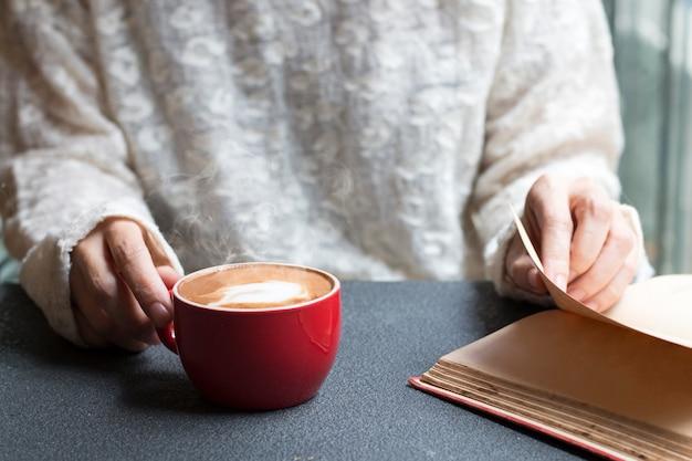 Donna delle mani che tiene il latte caldo della tazza di caffè vicino alla luce di mattina della finestra. Foto Premium