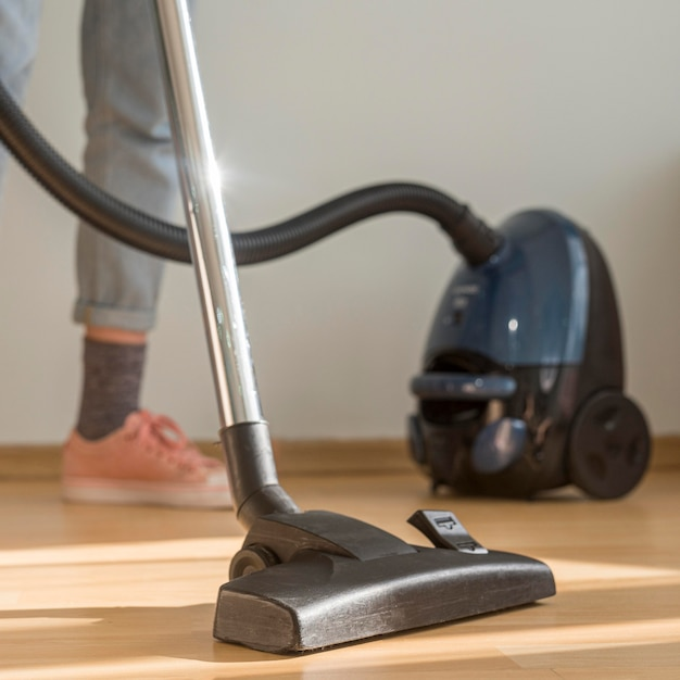 Donna delle pulizie con aspirapolvere Foto Gratuite