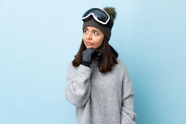 Donna dello sciatore della corsa mista con i vetri di snowboard sopra spazio blu isolato che ha dubbi e con l'espressione confusa del fronte Foto Premium