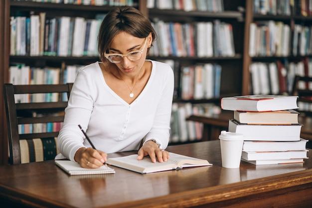 Donna dello studente che studia alla biblioteca e che beve caffè Foto Gratuite