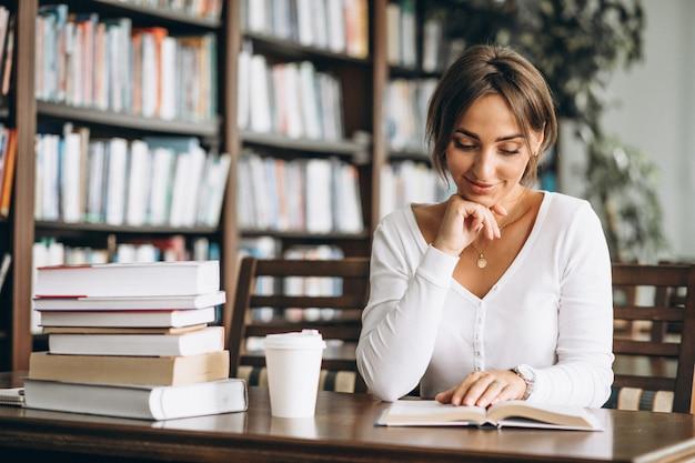 Donna dello studente che studia alla biblioteca Foto Gratuite