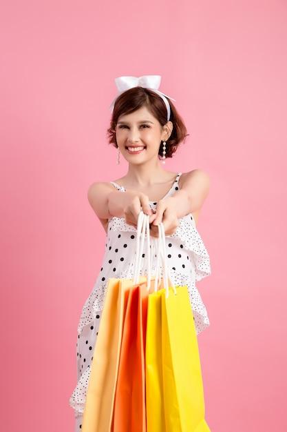 Donna di acquisto che tiene i sacchetti della spesa sul rosa Foto Gratuite