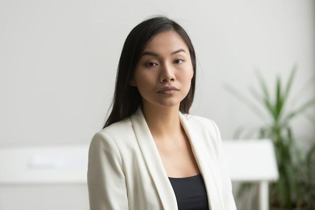 Donna di affari asiatica attraente sicura che esamina macchina fotografica, ritratto capo del colpo Foto Gratuite