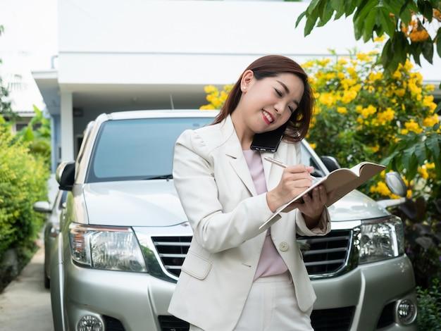 Donna di affari asiatica che parla sul telefono cellulare e che fa le note contro un'automobile. Foto Premium