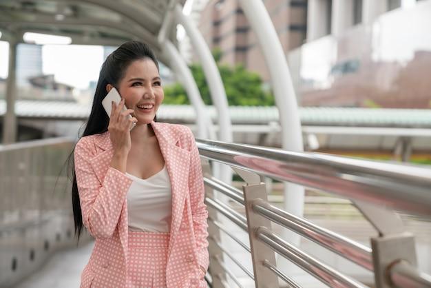 Donna di affari asiatica felice che sorride e che rivolge allo smartphone mentre camminando sulla via della città Foto Premium