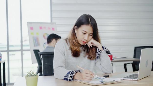 Donna di affari asiatica professionale che lavora al suo ufficio tramite computer portatile. Foto Gratuite