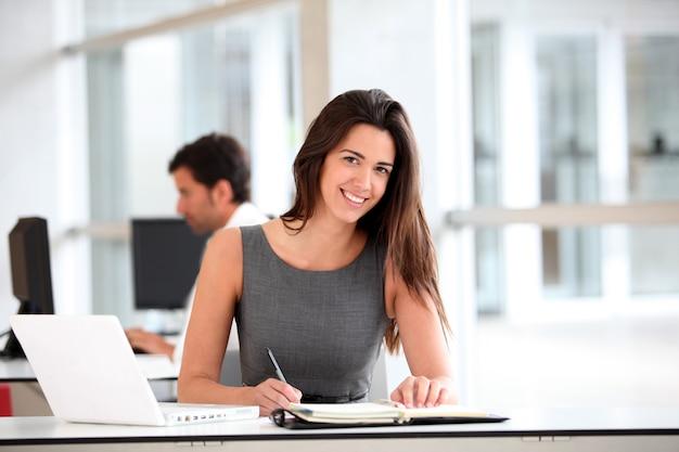 Donna di affari attraente che lavora al computer portatile Foto Premium