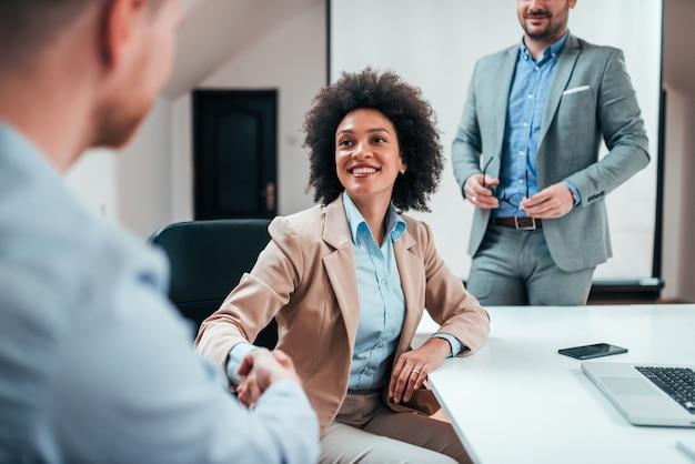 Donna di affari che agita le mani con l'altro impiegato su una riunione corporativa. Foto Premium