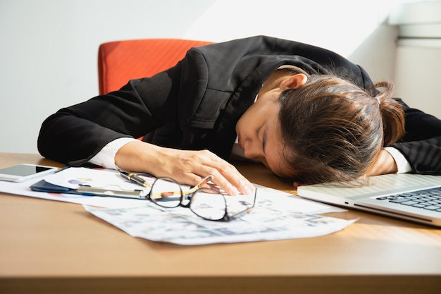 Donna di affari che dorme al scrittorio del lavoro con il computer portatile dopo l'ora di pranzo Foto Premium