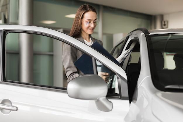 Donna di affari che entra in un'automobile Foto Gratuite