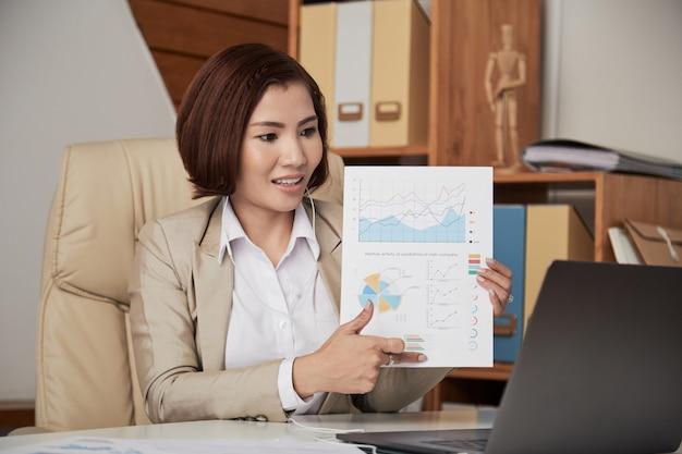 Donna di affari che ha conferenza online in ufficio Foto Gratuite