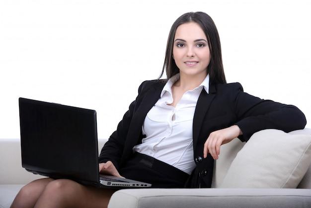 Donna di affari che lavora ad un computer portatile che si siede sul sofà. Foto Premium