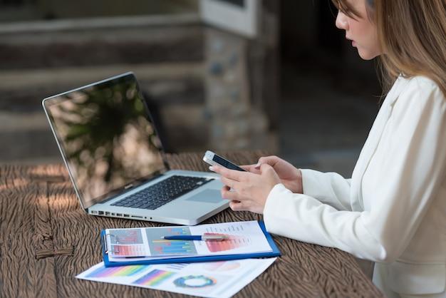 Donna di affari che lavora al computer portatile cercando e digitando sullo smartphone, si chiuda. Foto Premium