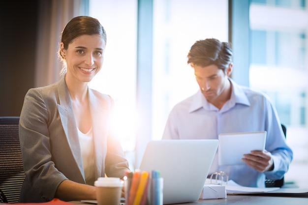 Donna di affari che lavora al computer portatile con il collega Foto Premium