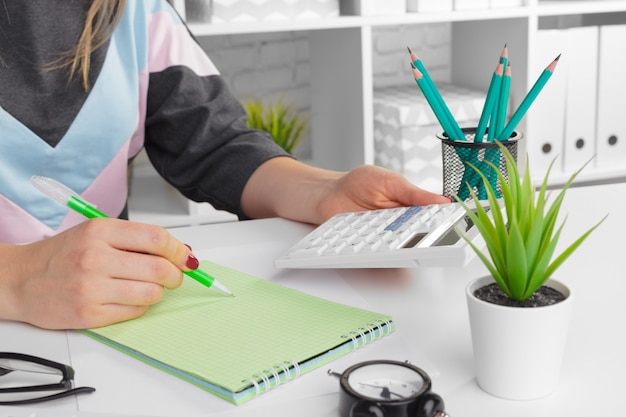 Donna di affari che lavora con la mano di dati finanziari facendo uso del calcolatore Foto Premium