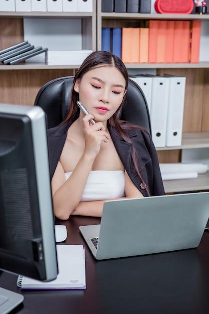 Donna di affari che lavora nell'ufficio con un sorriso mentre sedendosi. Foto Gratuite