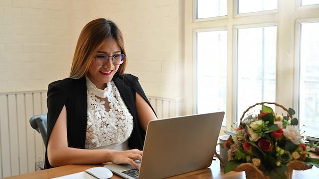 Donna di affari che per mezzo del computer portatile sulla tavola di legno. Foto Premium