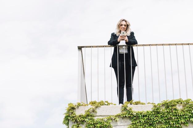 Donna di affari che per mezzo dello smartphone sul balcone Foto Gratuite
