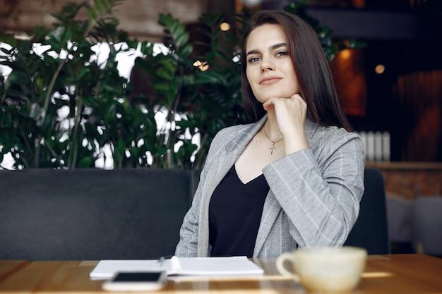 Donna di affari che si siede al tavolo in un caffè e di lavoro Foto Gratuite