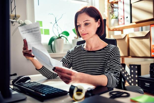 Donna di affari che si siede allo scrittorio e che legge posta all'ufficio Foto Premium