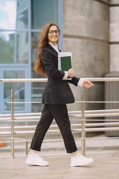 Donna di affari che sta all'aperto nell'edificio per uffici della città Foto Gratuite