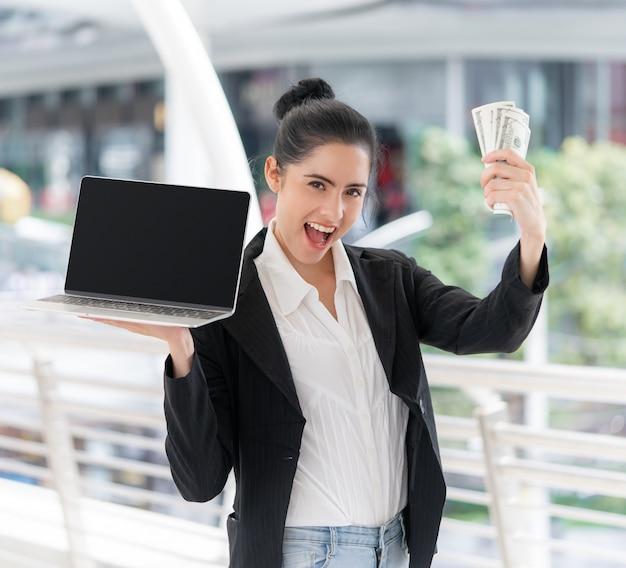 Donna di affari che tiene computer portatile in bianco Foto Premium