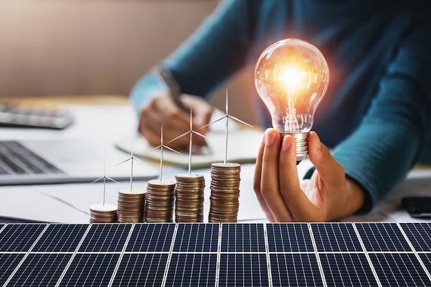 Donna di affari che tiene lampadina con la turbina sulle monete e sul pannello solare. concetto di risparmio energetico e contabilità finanziaria Foto Premium