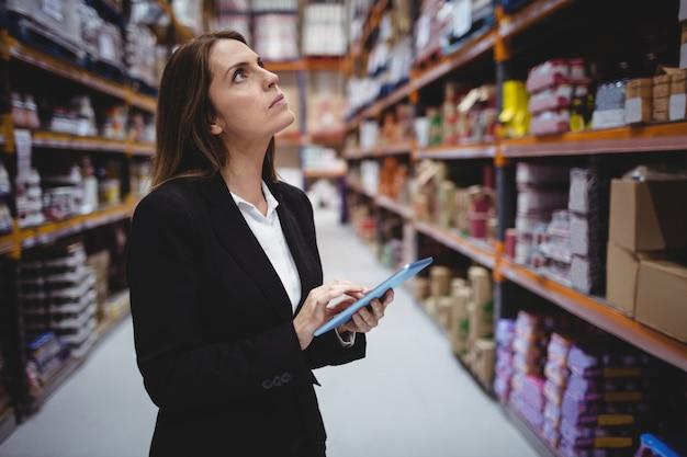 Donna di affari che utilizza compressa nel magazzino Foto Premium