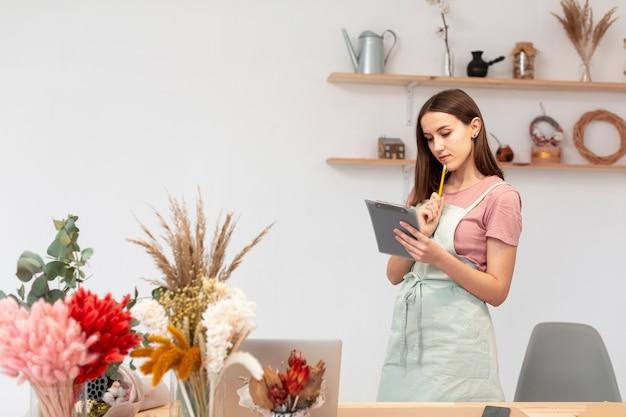 Donna di affari che utilizza una compressa digitale nel suo proprio negozio Foto Gratuite