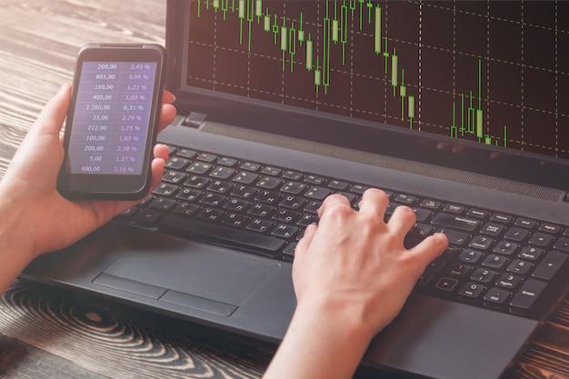 Donna di affari con il grafico del mercato finanziario di manifestazione dello smart phone, grafico del mercato finanziario di manifestazione del computer portatile, concetto del mercato azionario. Foto Premium