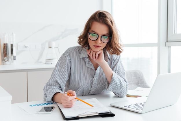 Donna di affari concentrata giovani in vetri e camicia a strisce che lavorano con le carte a casa Foto Gratuite