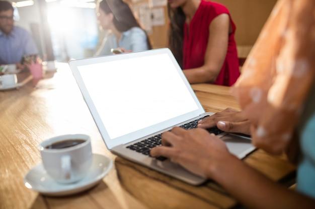 Donna di affari dei pantaloni a vita bassa che per mezzo di un computer portatile Foto Premium