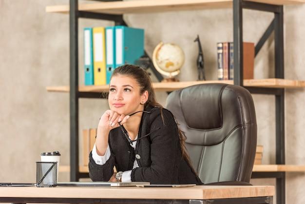 Donna di affari del brunette che pensa nel suo ufficio Foto Gratuite