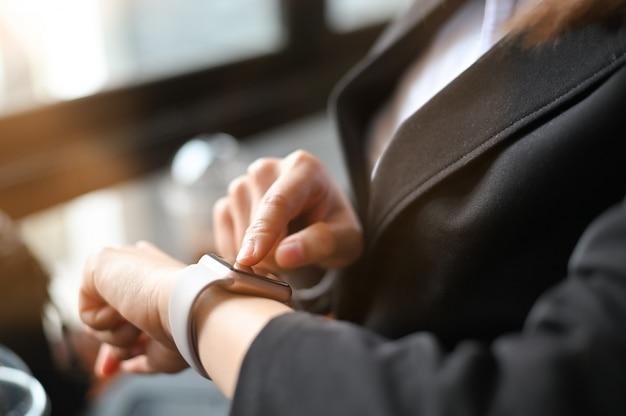 Donna di affari del primo piano che usando smartwatch. Foto Premium