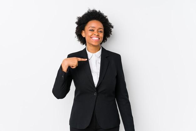 Donna di affari dell'afroamericano di mezza età contro una persona isolata bianca che indica a mano uno spazio della copia della camicia, fiero e sicuro Foto Premium