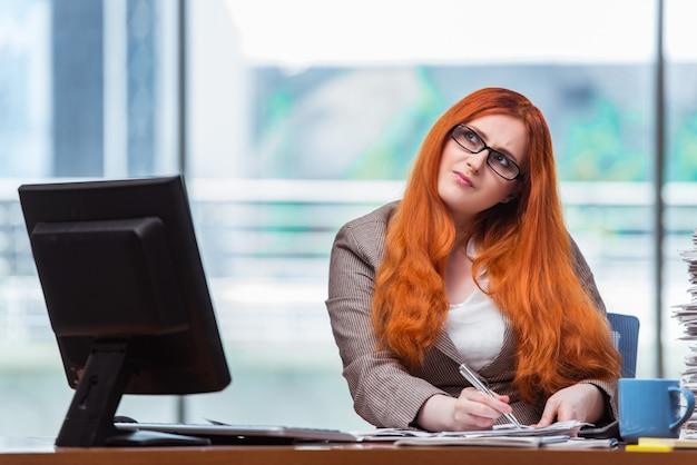 Donna di affari della testarossa che si siede al suo scrittorio nell'ufficio Foto Premium