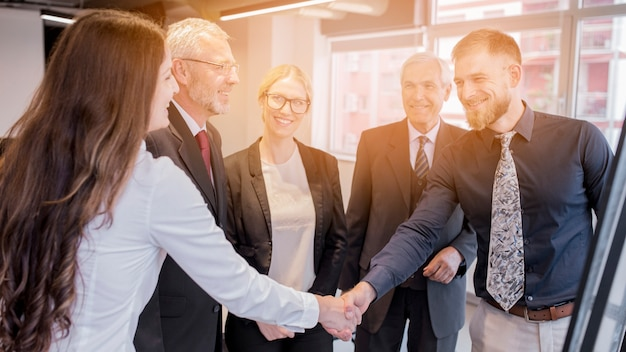 Donna di affari ed uomo d'affari che si stringono la mano l'un l'altro nella riunione Foto Gratuite