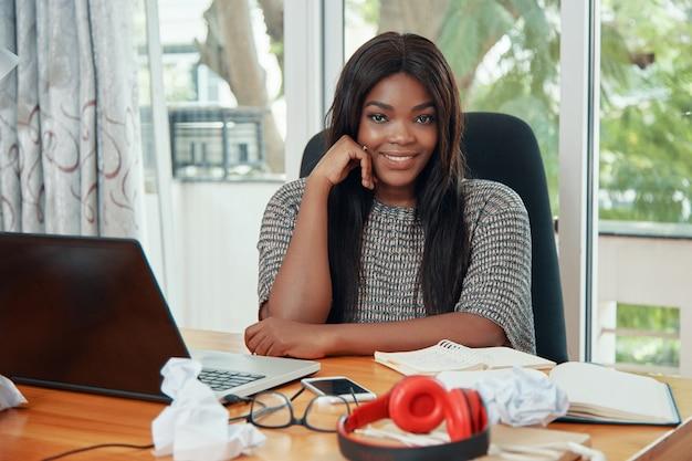 Donna di affari etnica sorridente al tavolo di lavoro Foto Gratuite