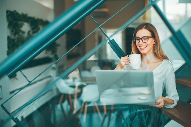 Donna di affari graziosa che si siede oh le scale dell'ufficio, avendo pausa caffè e web-surfing internet Foto Premium