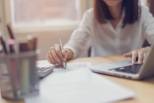 Donna di affari in ufficio e utilizzare computer e calcolatrice per eseguire la contabilità finanziaria. Foto Premium