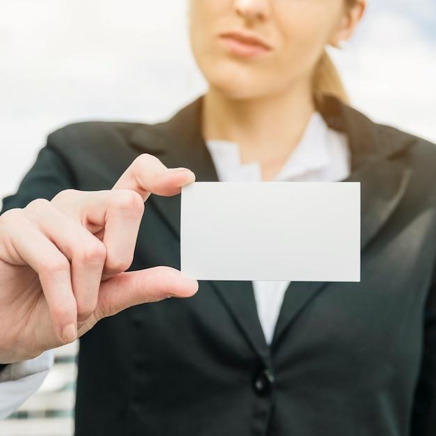 Donna di affari in vestito che mostra la carta bianca in bianco di visita Foto Gratuite