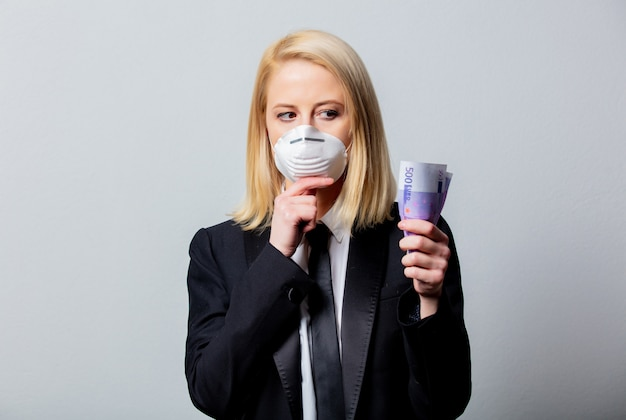 Donna di affari in vestito nero e maschera con soldi Foto Premium