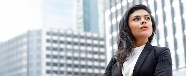 Donna di affari latina potente nella priorità bassa della bandiera dell'edificio per uffici della città Foto Premium