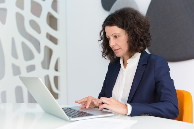Donna di affari messa a fuoco che lavora al computer Foto Gratuite