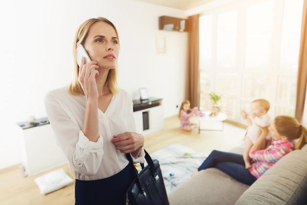Donna di affari mom talking phone in salotto Foto Premium