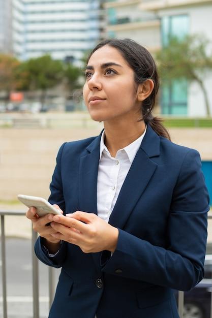 Donna di affari pensierosa che per mezzo dello smartphone Foto Gratuite