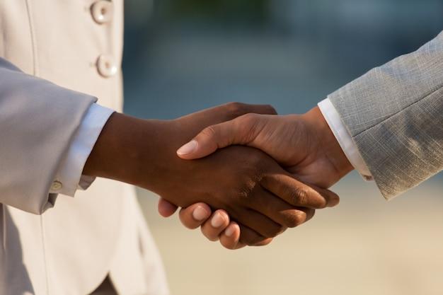 Donna di affari scura che stringe le mani con il collega maschio Foto Gratuite