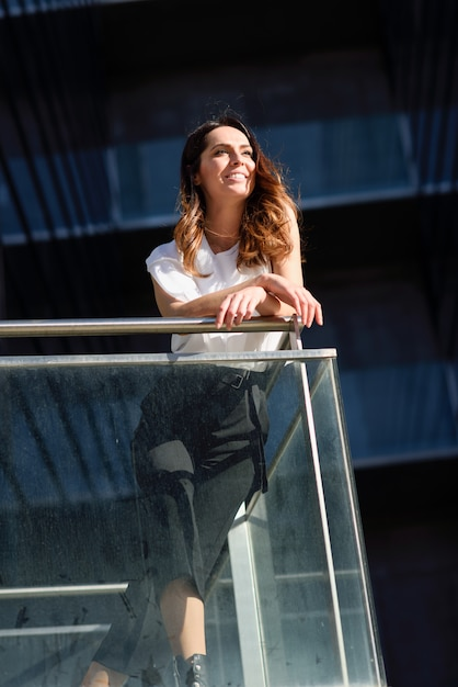Donna di affari sicura che sta fuori di un edificio per uffici. Foto Premium