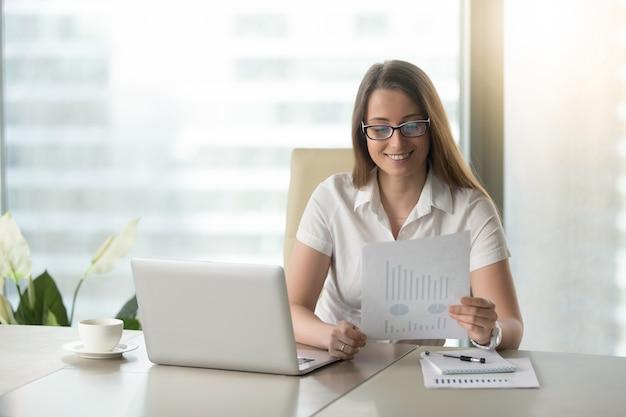 Donna di affari soddisfatta che rivede i risultati finanziari Foto Gratuite