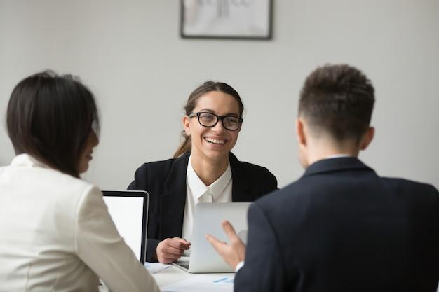 Donna di affari sorridente che parla con subordinato circa i rapporti Foto Gratuite